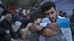 A Syrian refugee child sleeps on his father's arms while waiting at a resting point to board a bus, after arriving on a dinghy from the Turkish coast to the northeastern Greek island of Lesbos on Oct. 4, 2015. (AP / Muhammed Muheisen)