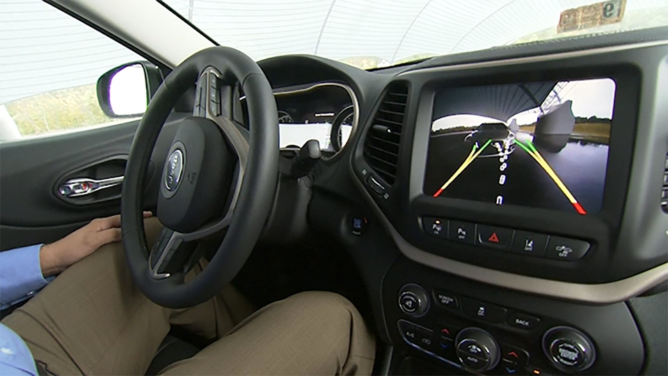 This image from video, taken Oct. 1, 2015, shows Insurance Institute for Highway Safety (IIHS) Senior Research Engineer David Aylor in the drivers seat with an electronic display on the dashboard for parallel parking assistance at the IIHS Vehicle Research Center in Ruckersville, Va. (AP/Dan Huff)