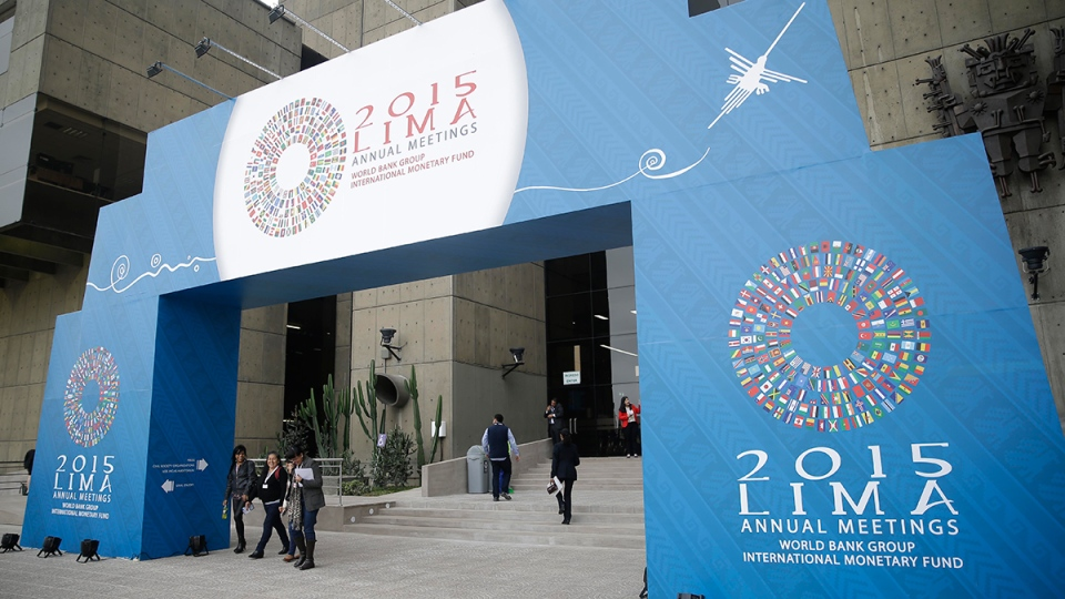 People pass under a welcome sign for the IMF and World Bank annual meetings in Lima, Peru, Tuesday, Oct. 6, 2015. (AP / Martin Mejia)