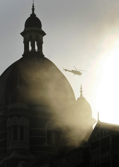 An Indian Army helicopter hovers as smoke comes out of the Taj Mahal hotel in Mumbai, India, on Thursday, Nov. 27, 2008. (AP / Gurinder Osan)