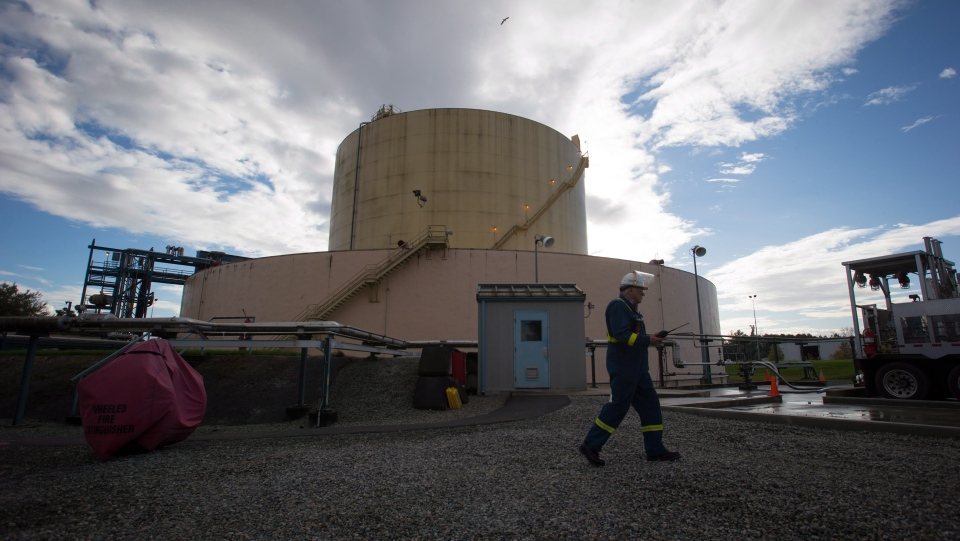 A FortisBC employee walks past a storage tank at the existing FortisBC Tilbury LNG facility before the groundbreaking for an expansion project in Delta, B.C., on October 21, 2014.  (Darryl Dyck / The Canadian Press)