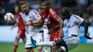Vancouver Whitecaps' Pa-Modou Kah, right, clears the ball away from FC Dallas' Tesho Akindele, centre, as Jordan Harvey, left, defends during the first half of an MLS soccer game in Vancouver, B.C., on Oct. 7, 2015. (Darryl Dyck / The Canadian Press)