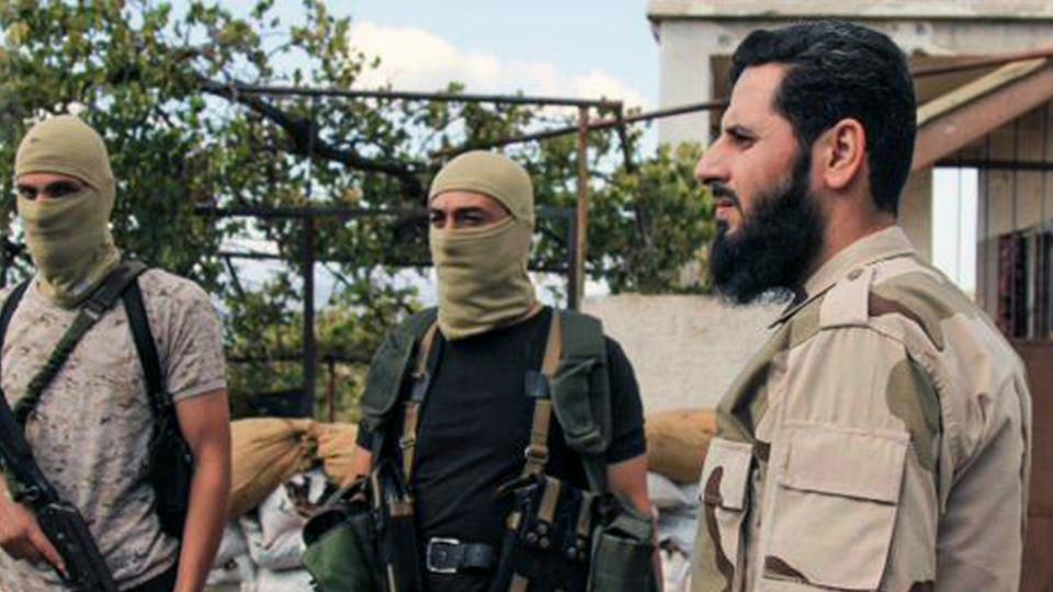 In this image posted on the Twitter page of Ahrar al-Sham, Ahrar al-Sham leader Muhannad al-Masri, right, a Hama native also known as Abu Yahya al-Hamawi, visits his group's positions during the Eid al-Adha Islamic feast near the coastal region of Syria on Sept. 28, 2015. (Ahrar al-Sham Twitter page via AP)