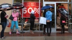 Shoppers stand outside the Kate Spade store at St. Louis Premium Outlets in Chesterfield, Mo. during a steady rain on Monday, Dec. 22, 2014. (AP Photo/St. Louis Post-Dispatch, Robert Cohen)