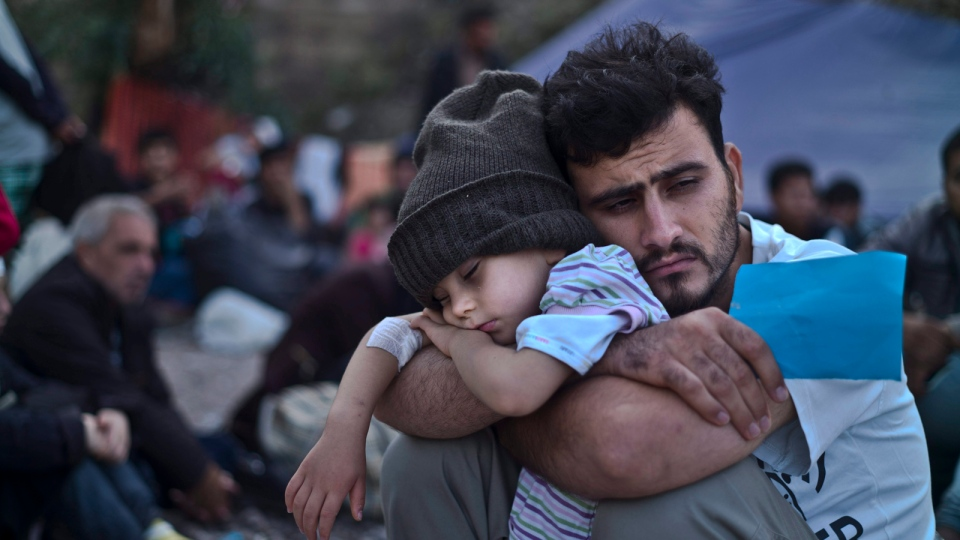 A Syrian refugee child sleeps on his father's arms while waiting at a resting point to board a bus, after arriving on a dinghy from the Turkish coast to the northeastern Greek island of Lesbos, Sunday, Oct. 4, 2015. (AP / Muhammed Muheisen)