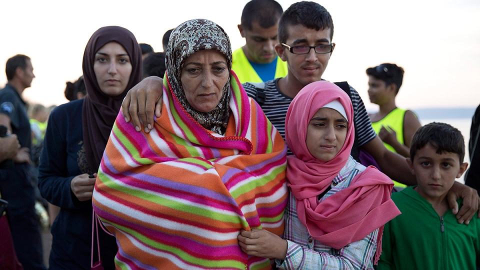 A Syrian family walks after they arrived with other refugees from Turkey to the shores of the Greek island of Lesbos, on an inflatable dinghy, Friday, Sept. 25, 2015. (AP / Petros Giannakouris / THE CANADIAN PRESS)