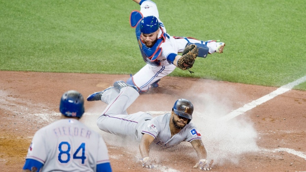 Texas Rangers' Delino DeShields, centre, slides safely into home plate past Toronto Blue Jays catcher Russell Martin during third inning game one American League Division Series baseball action in Toronto on Thursday, October 8, 2015. (Darren Calabrese / THE CANADIAN PRESS)