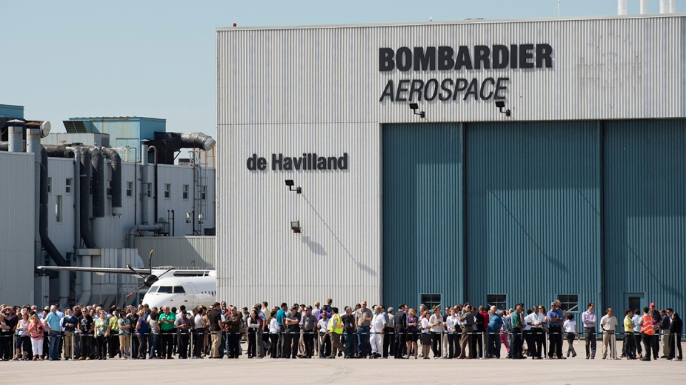 Employees line the tarmac to watch the fly-by of the new CS100 aircraft during an event at the Bombardier site in Toronto on Thursday, Sept. 10, 2015. (Darren Calabrese /  THE CANADIAN PRESS)