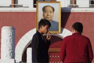 A man smokes near a portrait of late Chinese leader Mao Zedong hung on a replica of the Tiananmen Gate in Yinchuan in northwestern China's Ningxia Hui autonomous region on Thursday, Oct. 8, 2015. (AP / Ng Han Guan)