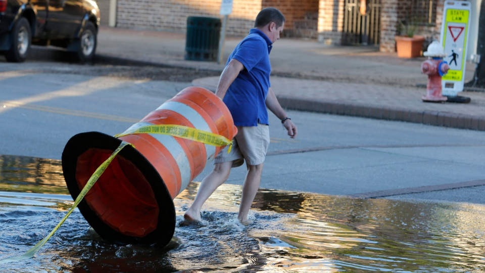 Harris Carter, owner of Castaways & Grill in the historic section of Georgetown, moves a road barrier to block traffic as high tide approaches historic downtown Georgetown, S.C., Thursday, Oct. 8, 2015. (AP / Mic Smith)