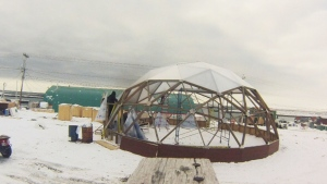 Construction is shown on a greenhouse in Naujaat, Nunavut.