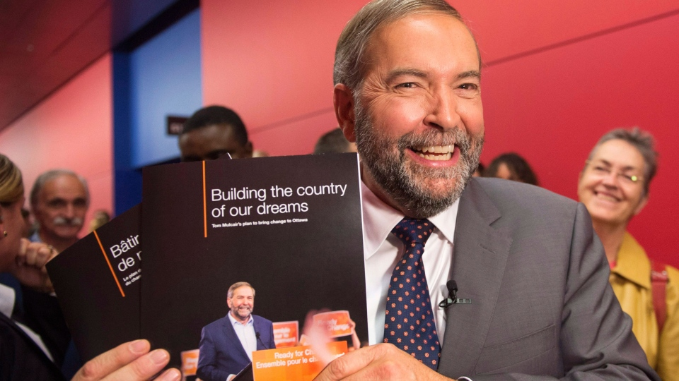NDP Leader Tom Mulcair holds up his party's platform book at a town hall meeting Friday, Oct. 9, 2015 in Montreal. (Ryan Remiorz / THE CANADIAN PRESS)