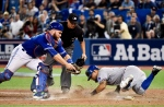 Toronto Blue Jays' catcher Russell Martin, left, attempts to tag Texas Rangers' Rougned Odor as he scores during 14th inning of game two American League Division Series baseball action in Toronto on Friday, Oct. 9, 2015. (Nathan Denette/THE CANADIAN)
