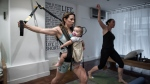 This photograph taken on October 6, 2015 shows mothers with their babies attending an exercise class dubbed 'Mumba', a new twist on the baby-wearing trend gripping mothers in the city. (AFP PHOTO / Philippe Lopez)