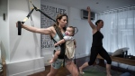 This photograph taken on Oct. 6, 2015 shows mothers with their babies attending an exercise class dubbed 'Mumba', a new twist on the baby-wearing trend gripping mothers in the city. (AFP PHOTO / Philippe Lopez)