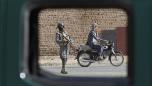 Afghan security forces are seen through the window of a police car after Taliban clashes in front of the district police station in the city of Kandahar, south of Kabul, Afghanistan, Thursday, Aug. 6, 2015. (AP / Allauddin Khan)