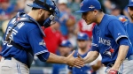 Toronto Blue Jays catcher Russell Martin (55) and relief pitcher Roberto Osuna (54) celebrate beating the Texas Rangers 8-4 at Game 4 of baseball's American League Division Series Monday, Oct. 12, 2015, in Arlington, Texas. (AP / Tony Gutierrez)