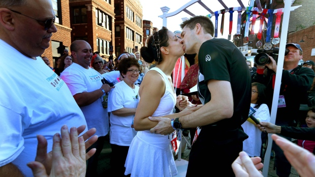 Stephanie Reinhart kisses Mark Jockel at their wedding during the Chicago Marathon, on Oct. 11. 2015. (Nancy Stone/Chicago Tribune via AP)