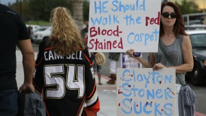 Animal rights activist Robyn Hicks, right, holds signs outside Honda Center to protest against Anaheim Ducks' Clayton Stoner before the Ducks' game with the Vancouver Canucks in Anaheim, Calif. on Monday, Oct. 12, 2015. (AP / Jae C. Hong)