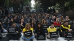The students of Ankara University hold the placards with the names of those killed in Saturday's deadly explosions during a sit-in protest in Ankara, Turkey, Tuesday, Oct. 13, 2015. (AP / Emrah Gurel)