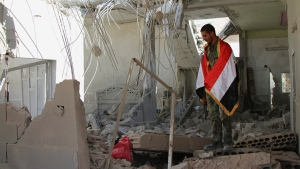 A Syrian soldier wrapped in a Syrian flag stands in a damaged house in Achan, Hama province, Syria, on Oct. 11, 2015. (Alexander Kots / Komsomolskaya Pravda via AP)