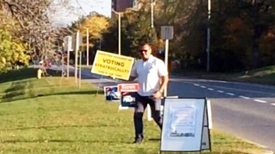 In this image from video, a man can be seen removing an election sign from the roadside in the riding of Kanata-Carleton, in Ottawa, Ont., over the Thanksgiving weekend.