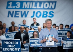 Conservative leader Stephen Harper holds a copy of his party's platform during a campaign stop in Richmond, B.C. Thursday, Oct. 9, 2015. (The Canadian Press/Jonathan Hayward)