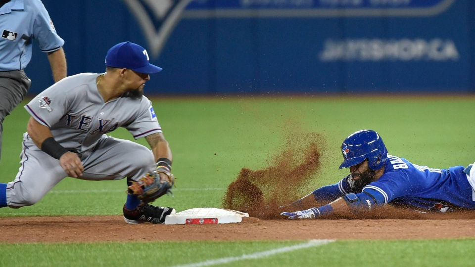 Toronto Blue Jays' Jose Bautista, right, slides safely into second base after hitting an RBI double in the 3rd inning of Game 5 of the ALDS in Toronto on Wednesday, Oct. 14, 2015. (Nathan Denette / THE CANADIAN PRESS)