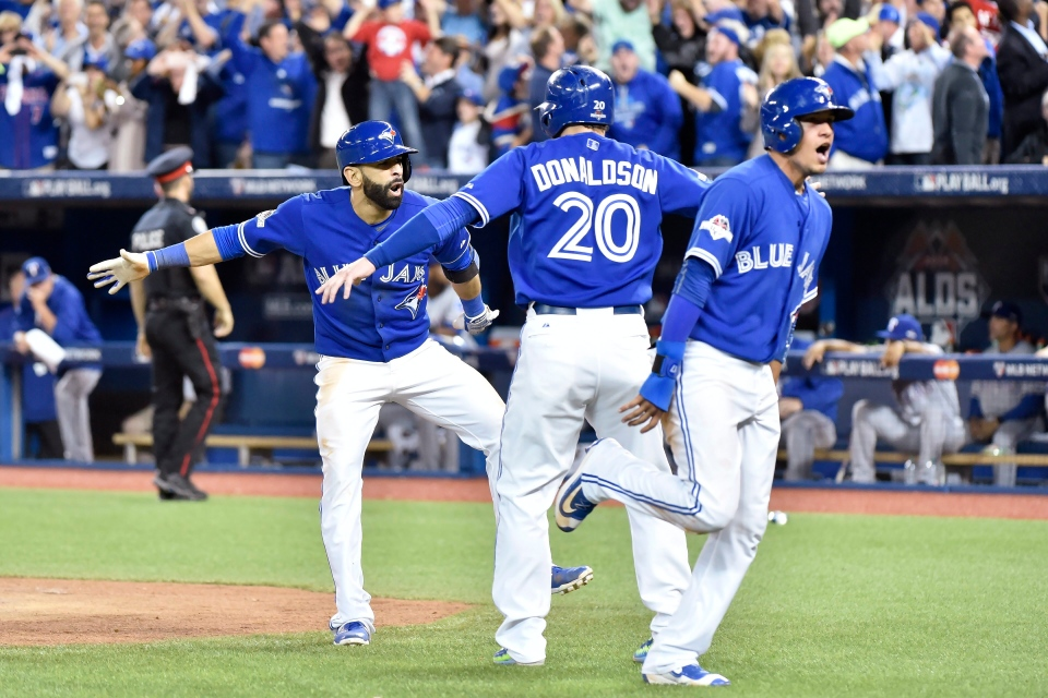 Jose Bautista celebrates his three-run homer with teammates Ryan Goins and Josh Donaldson during the 7th inning of Game 5 in the ALDS on Wednesday, Oct. 14, 2015. (Nathan Denette / THE CANADIAN PRESS)