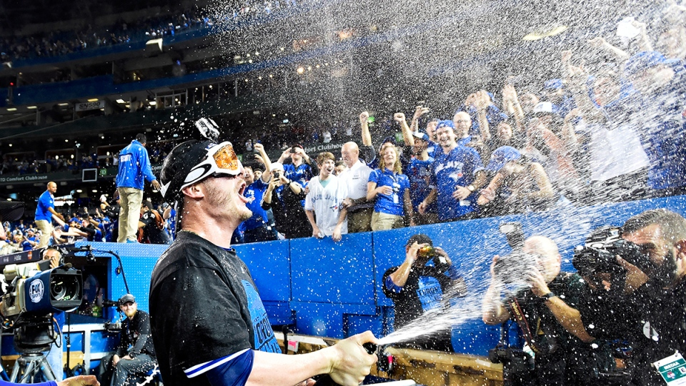Toronto Blue Jays third baseman Josh Donaldson sprays champagne on fans after defeating the Texas Rangers during the ALDS game five playoff baseball action in Toronto on Wednesday, Oct. 14, 2015. (Nathan Denette / THE CANADIAN PRESS)