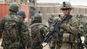 Afghan soldiers, left, walk past a U.S. Army soldier outside of a military base in Panjwai, Kandahar province south of Kabul, Afghanistan on Sunday, March 11, 2012. (AP / Allauddin Khan)