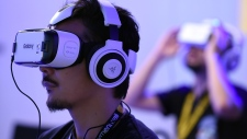 "People play with virtual reality head gear ""Gear VR"" of Oculus during the Tokyo Game Show in Chiba, a suburb of Tokyo. (AFP PHOTO / Toru YAMANAKA)"