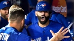 Toronto Blue Jays' Jose Bautista, right, celebrates his three-run home run with teammate Russell Martin during seventh inning game five American League Division Series playoff baseball action against the Texas Rangers in Toronto on Wednesday, October 14, 2015. (THE CANADIAN PRESS/Nathan Denette)