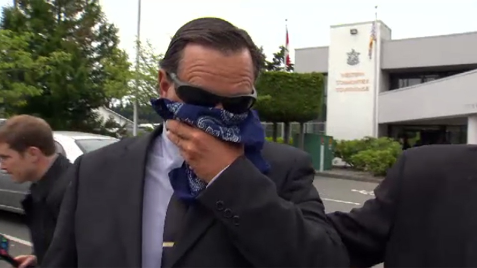 Dale Sheets covers his face as he exits Western Communities Provincial Court in Colwood after he was charged with child pornography-related offenses, June 19, 2014. (CTV Vancouver Island)