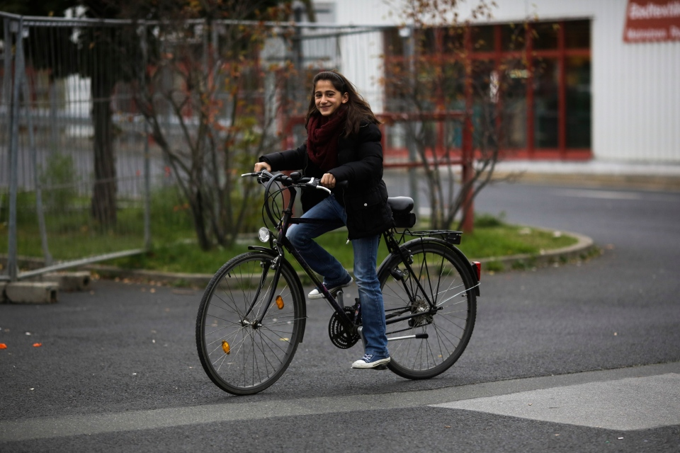 Syrian refugee Raghad Habashieh tests a bicycle organized by German volunteers for her family outside the refugee camp in Heidenau, Germany, Tuesday, Oct. 13, 2015. (AP / Markus Schreiber)