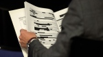 A reporter holds a redacted copy of the Doiron report released at a news conference by Brig.-Gen. Mike Rouleau in Ottawa, Tuesday, May 12, 2015. (THE CANADIAN PRESS/Adrian Wyld)