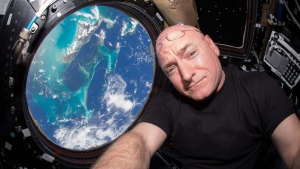 This July 12, 2015 photo, astronaut Scott Kelly poses for a selfie photo in the 'Cupola' of the International Space Station. On Friday, Oct. 16, 2015, Kelly broke the U.S. record for the most time spent in space Friday at 382 days. (Scott Kelly / NASA via AP)