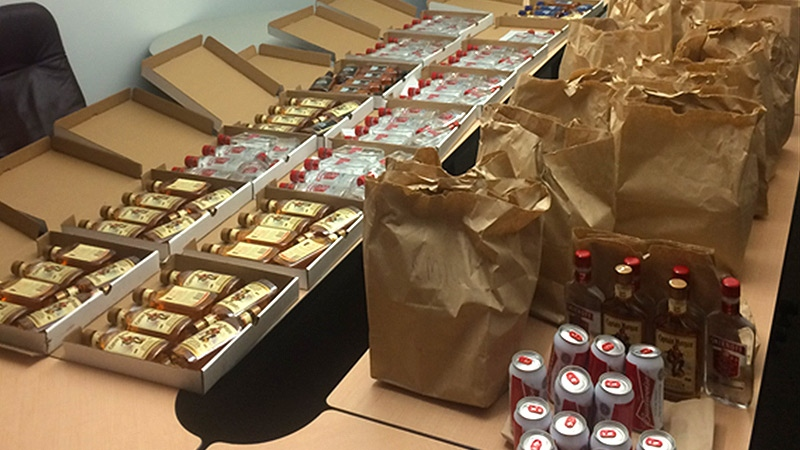 240 cans of beer and 100 bottles of spirits were found inside pizza boxes and brown paper bags. Supplied.