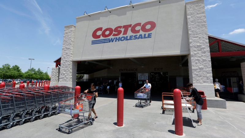 In this June 4, 2014 photo, shoppers push carts out of a Costco in Plano, Texas. (AP Photo/LM Otero)