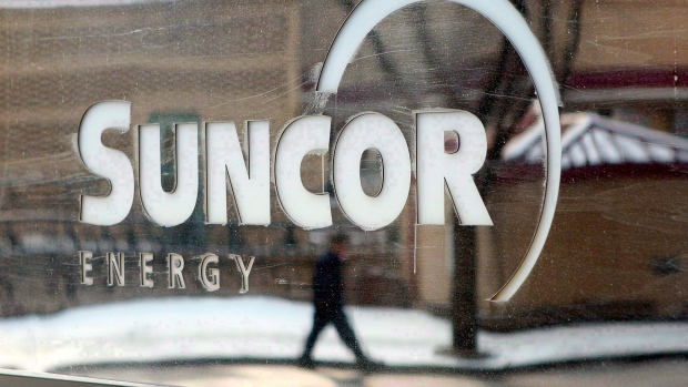 A pedestrian is reflected in a Suncor Energy sign in this photo taken in Calgary on Feb. 1, 2010. (Jeff McIntosh/THE CANADIAN PRESS)