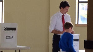 Justin Trudeau and his son in a polling station on Monday, Oct. 19, 2015 (CTV Montreal/Natalie Nanowski)