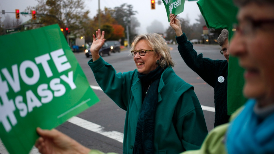 Green Party Leader Elizabeth May, starts election day by greeting drivers in the Saanich area with supporters at the intersection of Quadra St. and McKenzie Ave. in Victoria, B.C., Monday, October 19, 2015. (THE CANADIAN PRESS/Chad Hipolito)