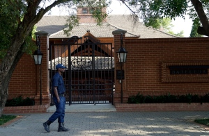 A security officer walks across the the house of Oscar Pistorius' uncle in Pretoria, South Africa, Tuesday, Oct. 20, 2015. (AP / Themba Hadebe)