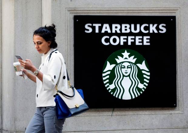 In this July 16, 2015 photo, a customer walks out of a Starbucks with a beverage in hand, in New York. Starbucks reports quarterly financial results on Thursday, July 23, 2015. (AP Photo/Mark Lennihan)