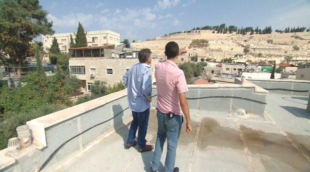 Ahmad Muna on the rooftop of his family's compound taking in the view of a new settlement overlooking the East Jerusalem neighbourhood. (David Iacolucci/CTV News)