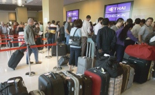 Tourists queue up at a temporary check-in counter set up at a hotel in downtown Bangkok, Thailand Monday, Dec. 1, 2008. Tourists are to fly from U-Tapao airport, south of Bangkok. (AP / Apichart Weerawong)