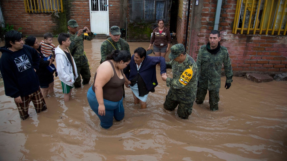 Soldiers help a woman to leave her flooded house to take her to a shelter in Zoatlan, Mexico, Saturday, Oct. 24, 2015. (AP / Eduardo Verdugo)