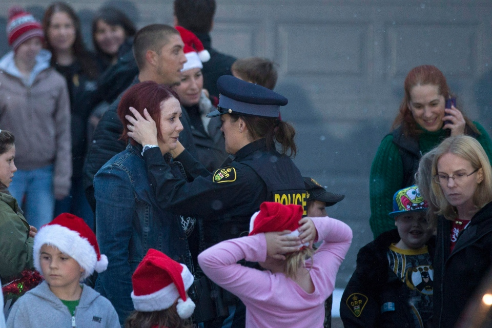 Evan Leversage's mother Nicole Wellwood is hugged by an OPP officer outside the family home before a Christmas Parade in St. George, Ontario on Saturday October 24, 2015. (Chris Young / THE CANADIAN PRESS)