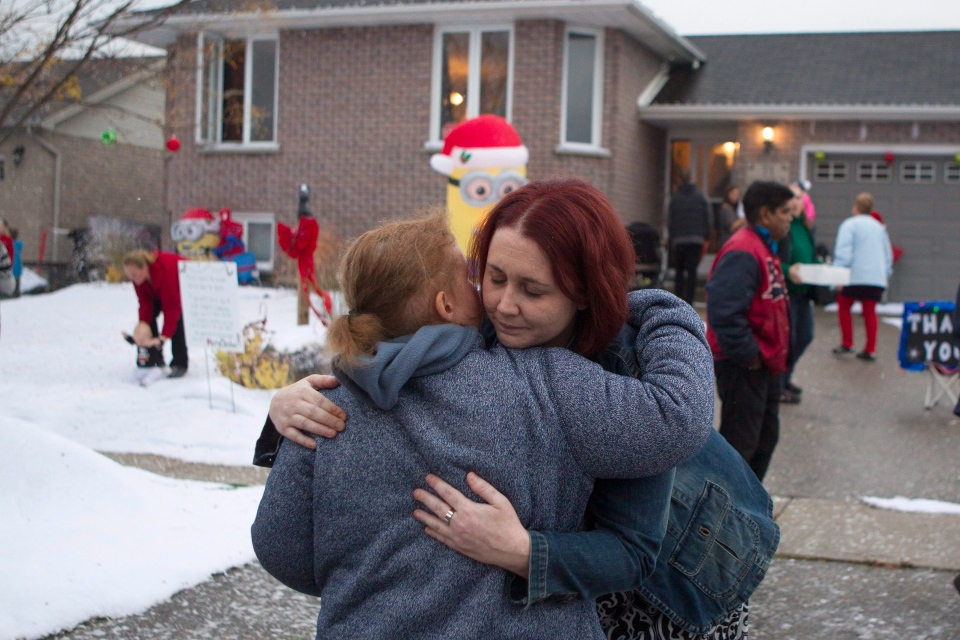 Evan Leversage's mother Nicole Wellwood is hugged by brain cancer survivor and well wisher Alicia Thibault outside the family home before a Christmas Parade in St. George, Ontario on Saturday October 24, 2015. (Chris Young / THE CANADIAN PRESS)