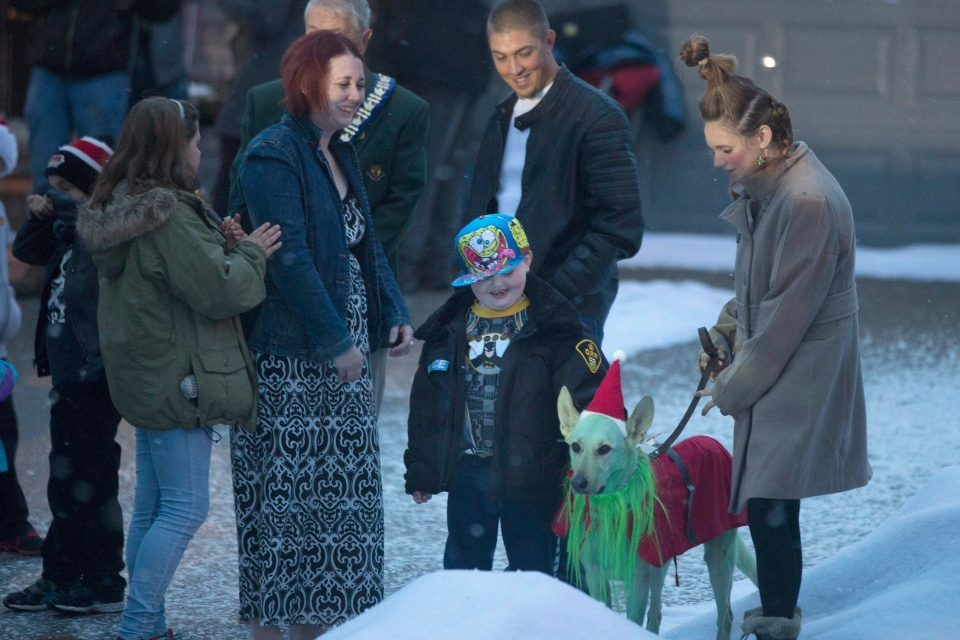 Evan Leversage (centre) pats a dog outside his family home as he stands with his with mother Nicole Wellwood (centre left) and father Travis Leversage before going to a ride in a police car ahead of watching a Christmas Parade in St. George, Ontario on Saturday October 24, 2015. (Chris Young / THE CANADIAN PRESS)
